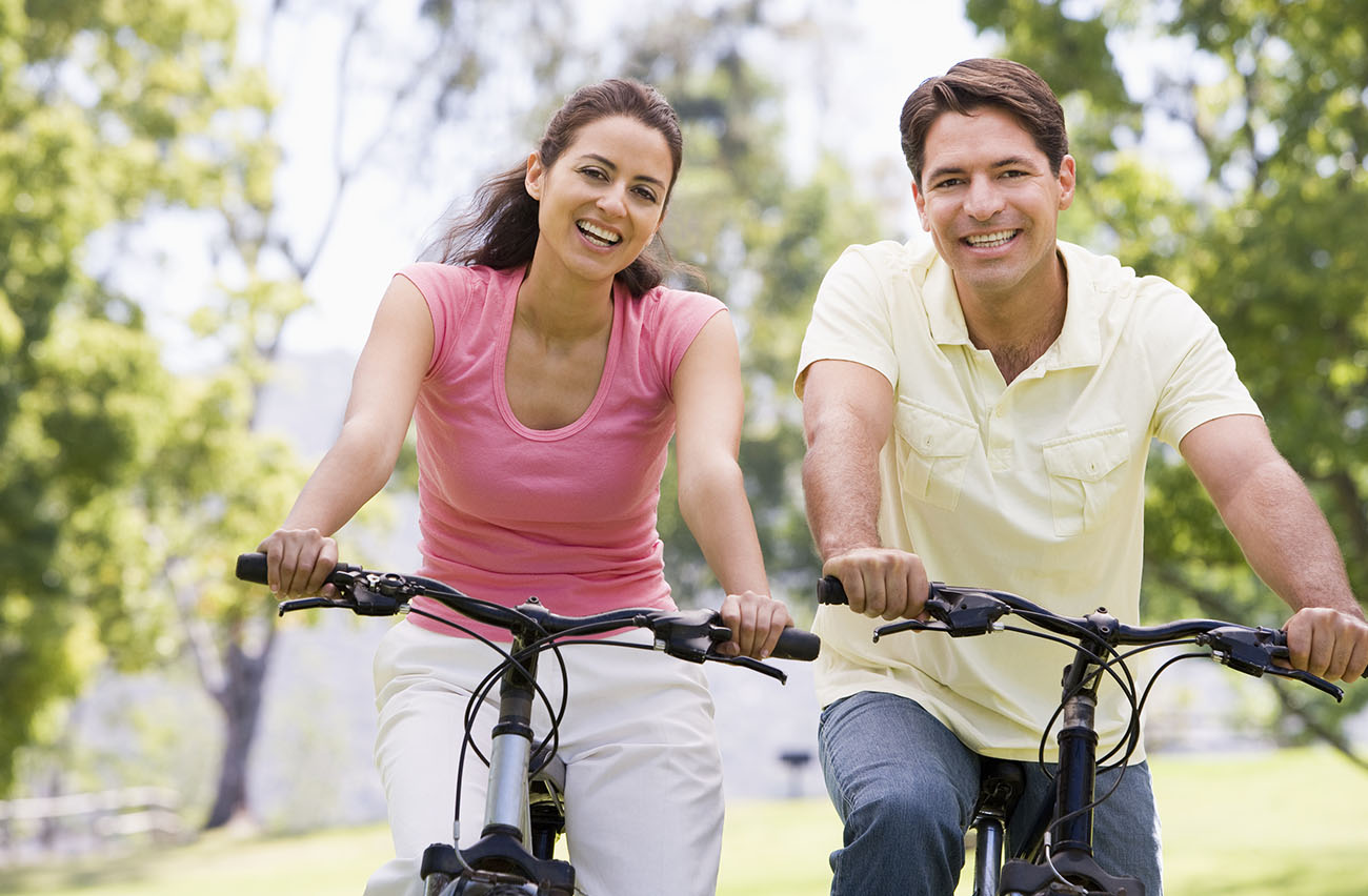 Happy healthy couple riding bikes
